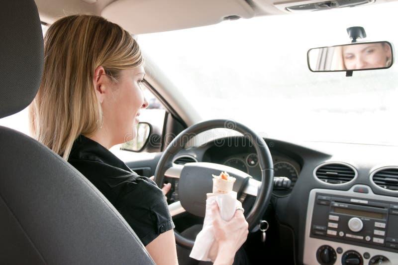 Portret van het jonge vrouw eten terwijl het drijven van auto royalty-vrije stock afbeeldingen