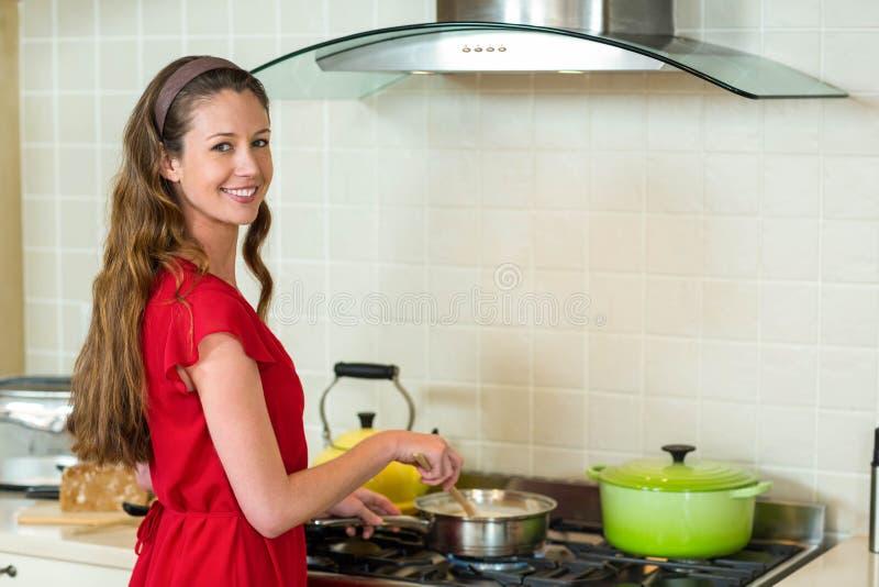 Portret van het jonge vrouw koken in keuken stock fotografie