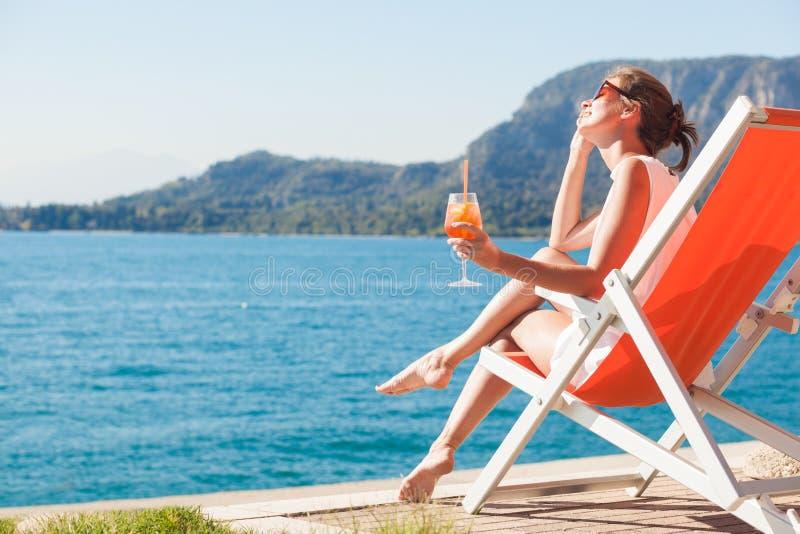 Portret van het jonge vrouw ontspannen in chaise zitkamer en het drinken Aperol Spritz cocktail in Lago Di Garda stock afbeeldingen