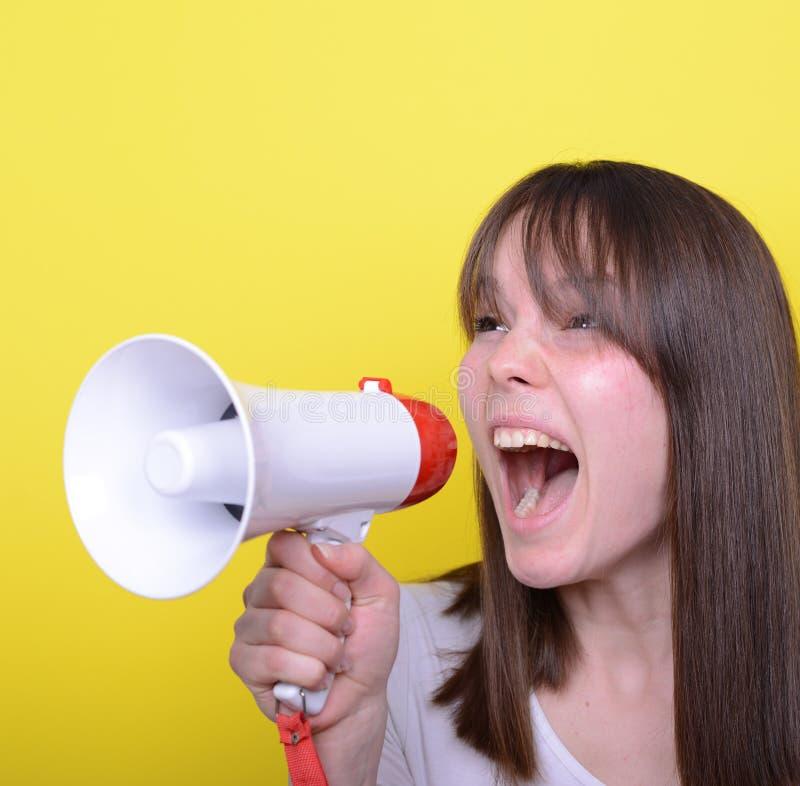 Portret van het jonge vrouw schreeuwen met een megafoon tegen geel royalty-vrije stock afbeelding