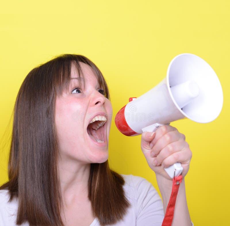 Portret van het jonge vrouw schreeuwen met een megafoon tegen geel stock afbeelding