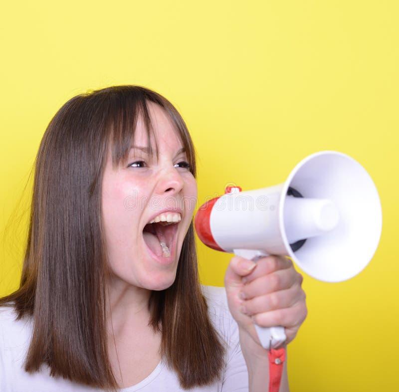 Portret van het jonge vrouw schreeuwen met een megafoon tegen geel royalty-vrije stock afbeeldingen