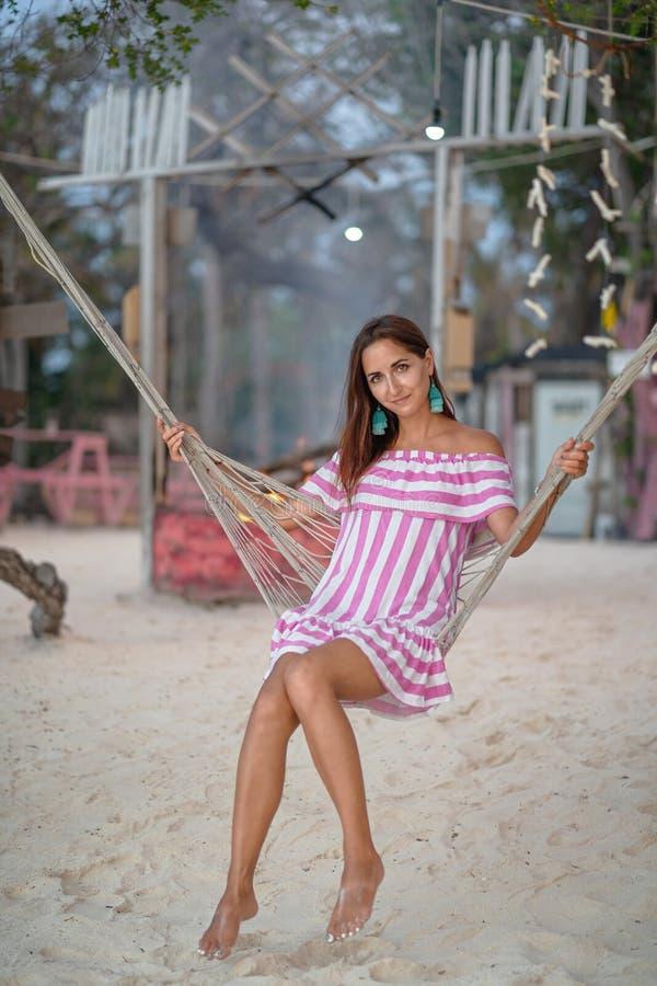 Portret van het jonge vrouw stellen in een hangmat op de achtergrond van het kustkamp stock foto