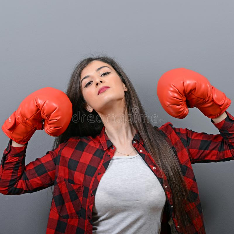 Portret van het jonge vrouw stellen met bokshandschoenen tegen grijze achtergrond stock afbeeldingen
