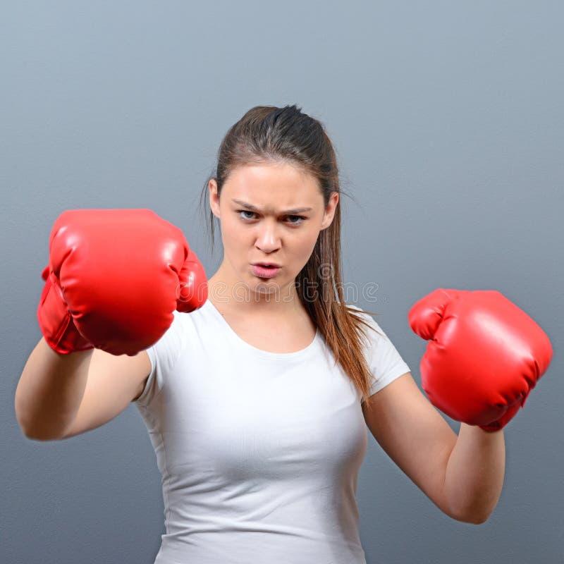 Portret van het jonge vrouw stellen met bokshandschoenen tegen grijze achtergrond stock afbeelding