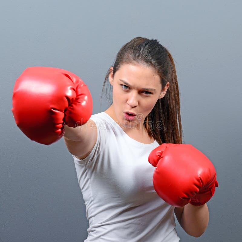 Portret van het jonge vrouw stellen met bokshandschoenen tegen grijze achtergrond stock fotografie