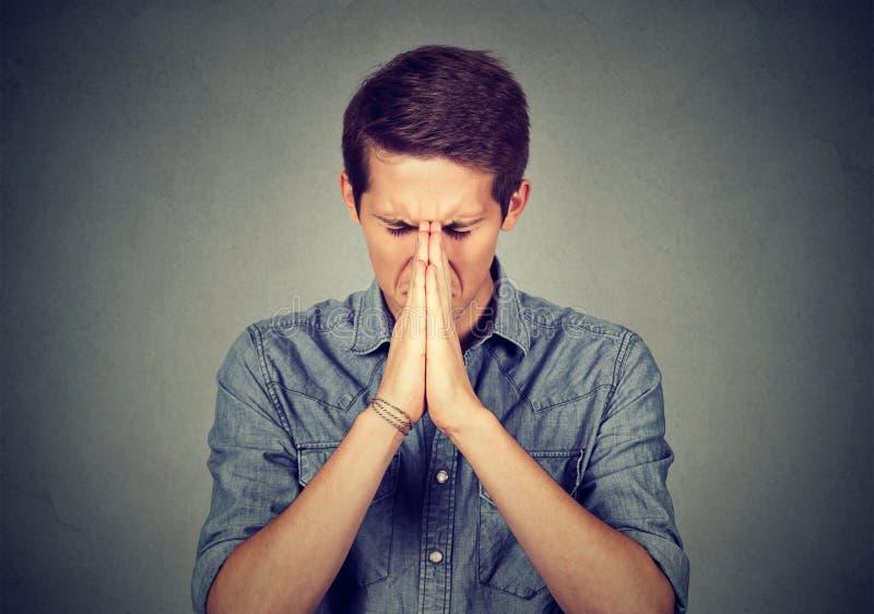 Portret van het jonge wanhopige mens bidden stock afbeelding