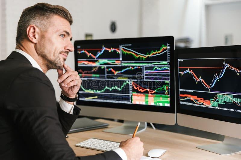 Portret van het Kaukasische zakenman werken in bureau en het kijken op computer met grafiek en grafieken stock foto's