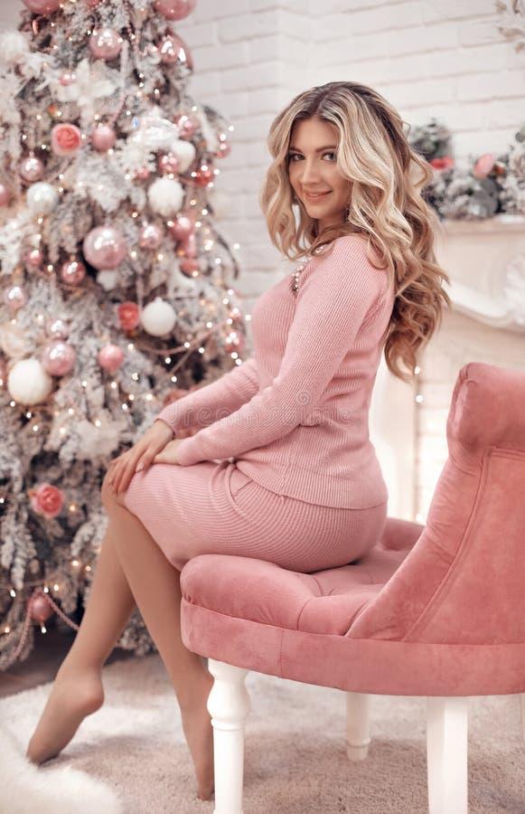 Portret van het Kerstmis het mooie meisje Mooie vrouwelijke huidige giftdoos Gelukkige Blondevrouw in roze doek met lange haarzit stock afbeeldingen