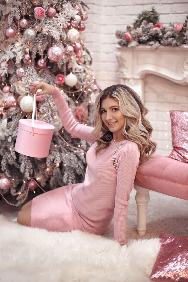 Portret van het Kerstmis het mooie meisje Mooie vrouwelijke huidige giftdoos Gelukkige Blondevrouw in roze doek met lange haarzit stock foto's