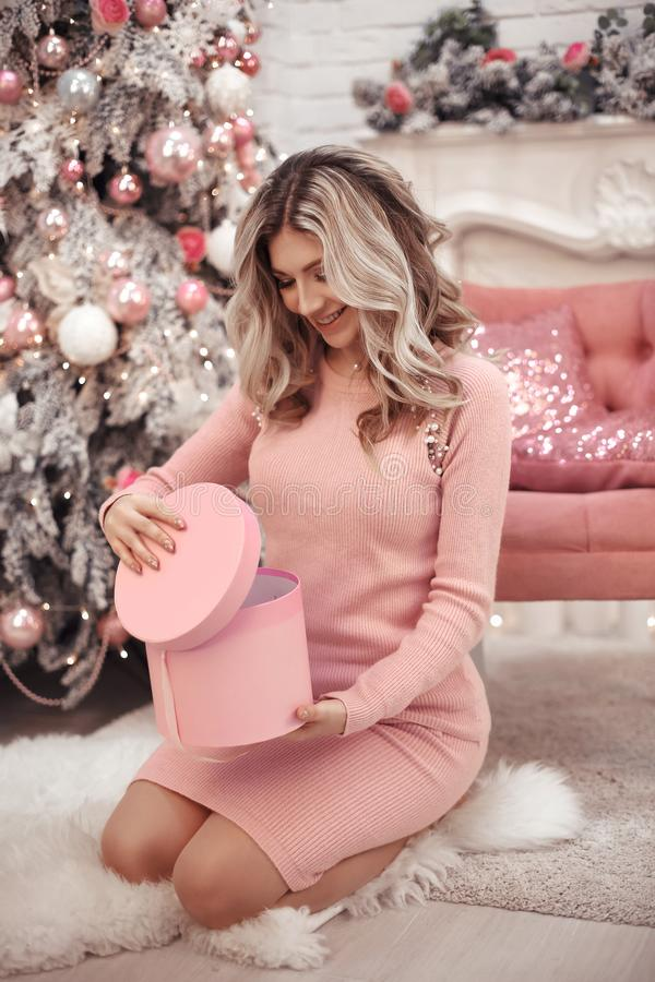 Portret van het Kerstmis het mooie meisje Mooie vrouwelijke huidige giftdoos Gelukkige Blondevrouw in roze doek met lange haarzit stock afbeelding