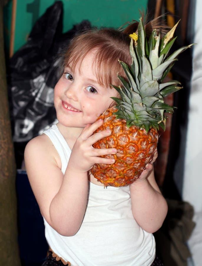 Portret van het kleine glimlachende meisje met een grote ananas royalty-vrije stock foto's