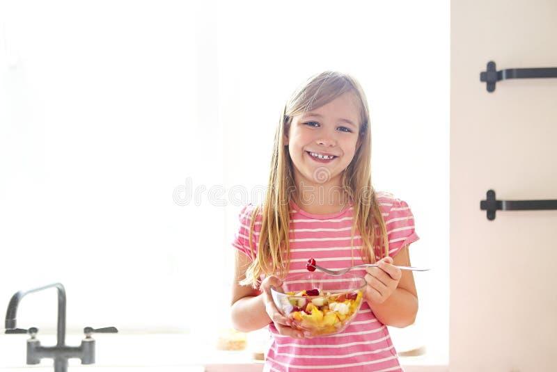 Portret van het kleine leuke meisje die verse fruitsalade eten royalty-vrije stock afbeelding