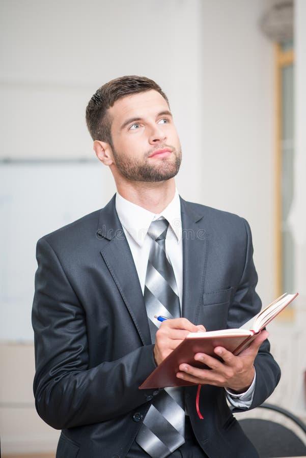 Portret van het knappe zekere zakenman schrijven stock fotografie