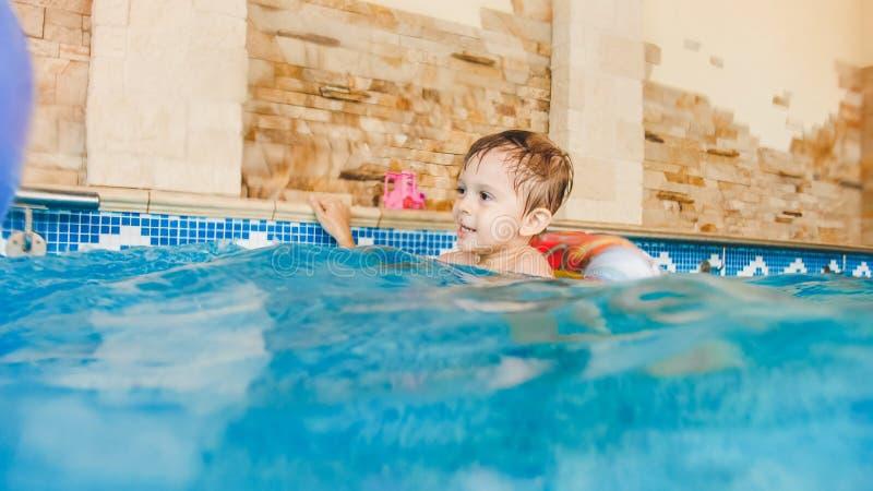 Portret van het lachen en het glimlachen van 3 jaar oud weinig jongen die met opblaasbare kleurrijke ring zwemmen en met strand s royalty-vrije stock foto's