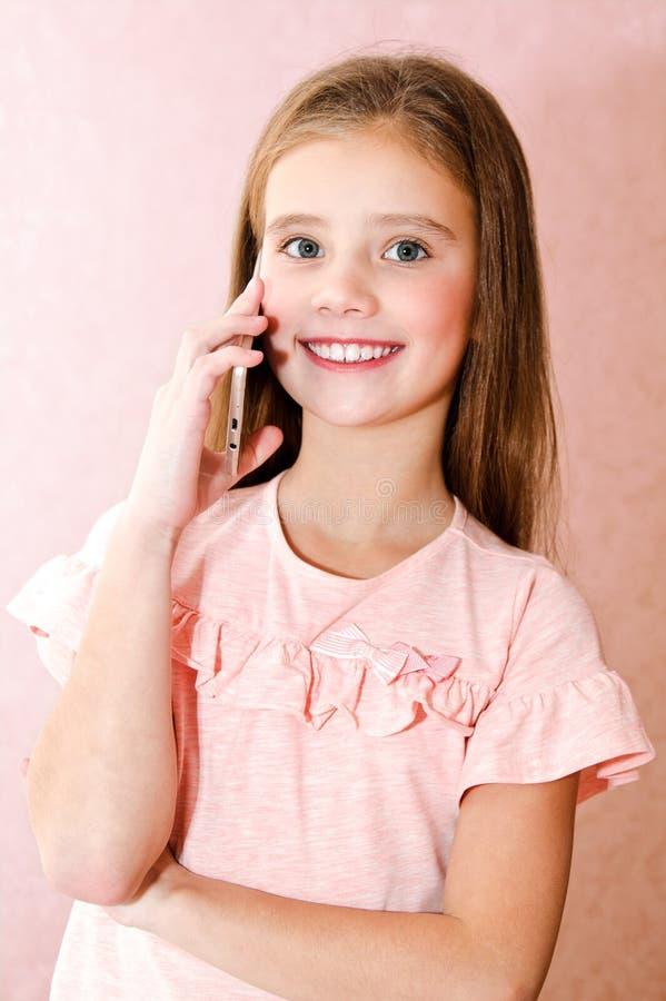 Portret van het leuke het glimlachen meisje roepen door smar celtelefoon stock foto