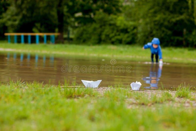 Portret van het leuke jong geitjejongen spelen met met de hand gemaakt schip kleuterschooljongen die een stuk speelgoed boot vare stock afbeeldingen
