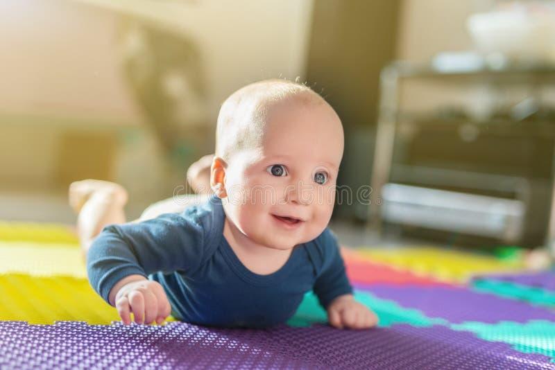 Portret van het leuke Kaukasische babyjongen kruipen op zachte het spelen mat binnen Aanbiddelijk kind die pret hebben die het ma royalty-vrije stock foto's