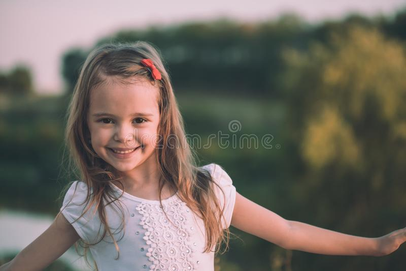 Portret van het leuke meisje glimlachen in de weide wordt geschoten die royalty-vrije stock afbeeldingen