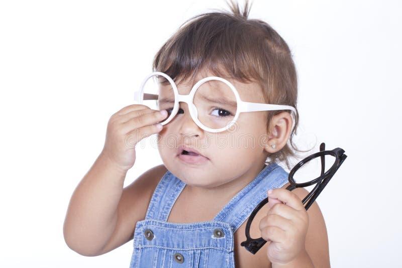 Portret van het leuke meisje proberen op glazen royalty-vrije stock afbeelding