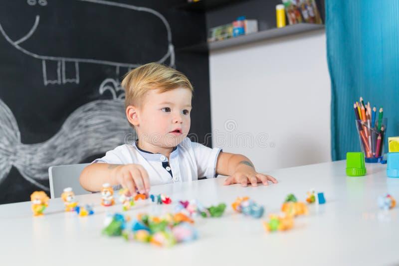 Portret van het leuke peuterjongen spelen met speelgoed bij het bureau thuis royalty-vrije stock foto's
