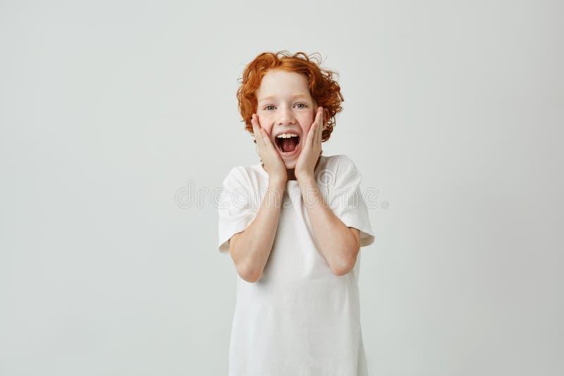 Portret van het leuke rode haired kind gillen met gelukkige uitdrukking toen de vader hem weinig puppy als Kerstmis gaf stock fotografie