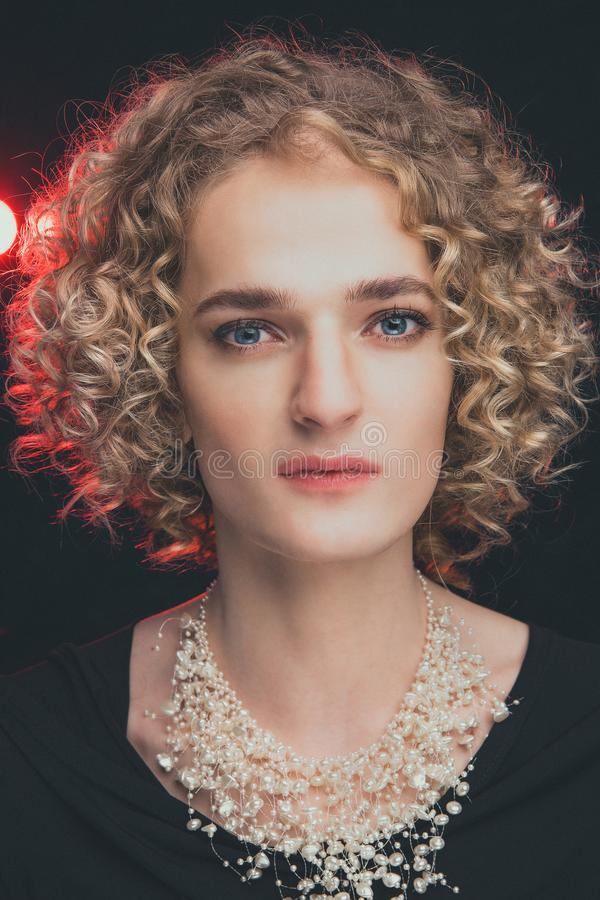 portret van het model van de transsexueelkerel met blauwe ogen en blond haar in het beeld van een meisje met parels rond hals, stock foto