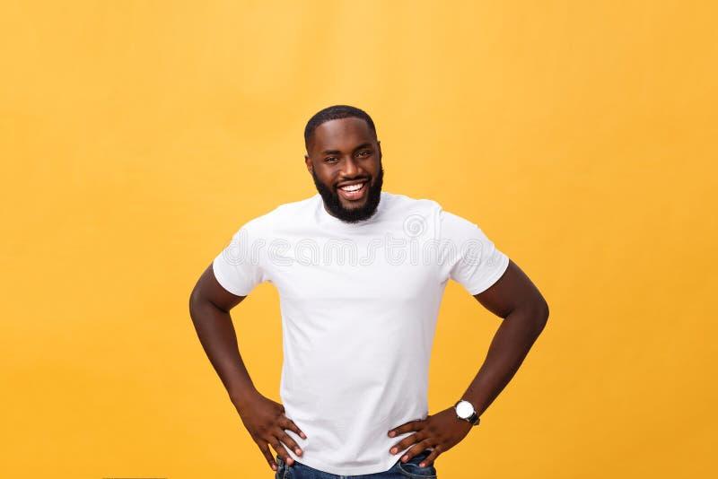 Portret van het moderne jonge zwarte mens glimlachen die zich op geïsoleerde gele achtergrond bevinden stock afbeeldingen