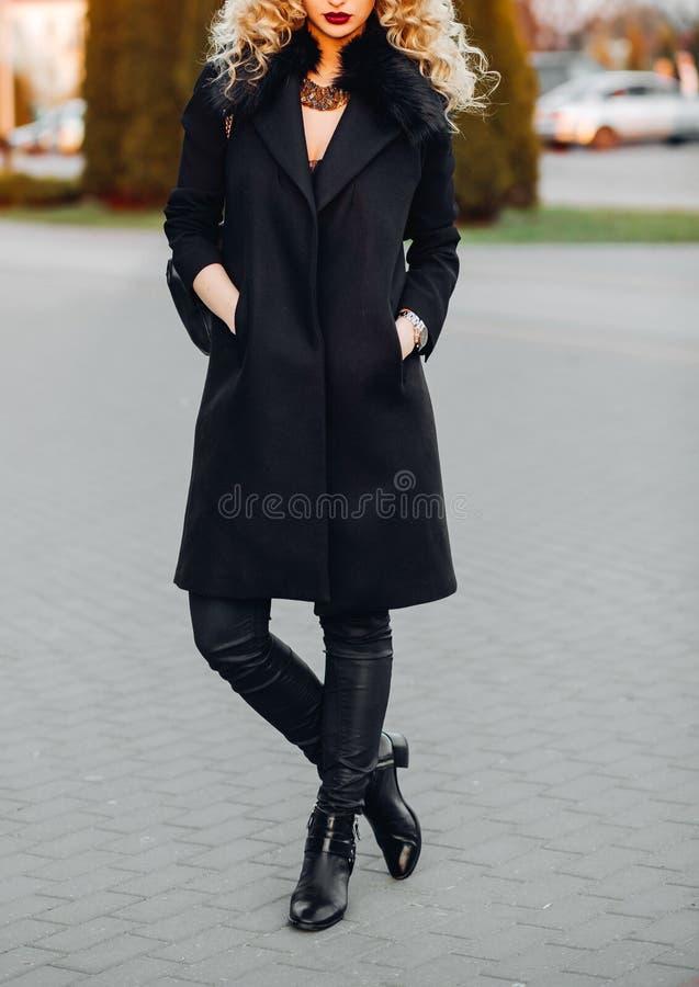 Portret van het modieuze vrouw stellen in openlucht in een zwarte tendens van de de herfstlaag, beenkappen, dalingslaarzen, een h royalty-vrije stock fotografie