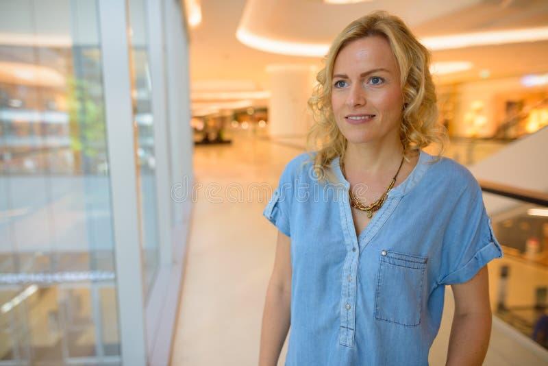 Portret van het mooie blondevrouw kijken door venster stock afbeeldingen