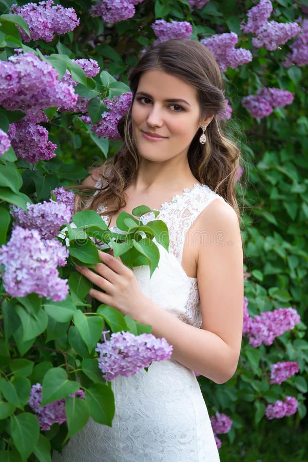 Portret van het mooie bruid stellen dichtbij bloeiende lilac boom royalty-vrije stock fotografie
