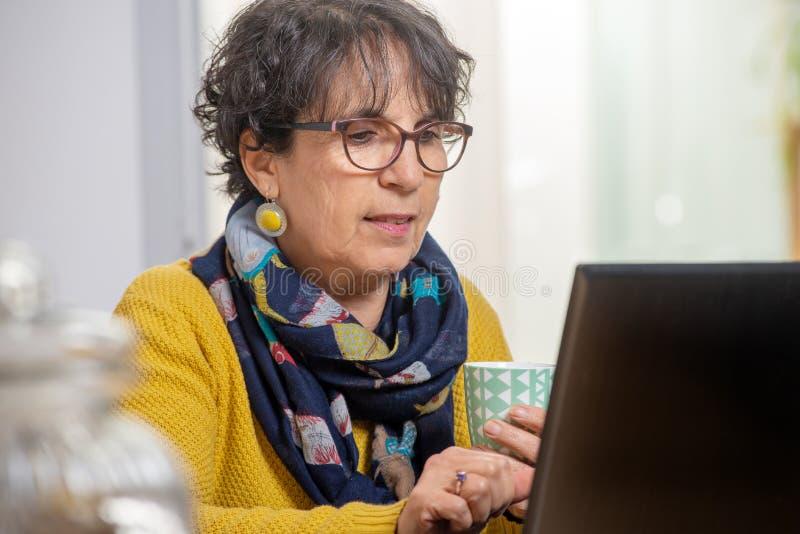 Portret van het mooie donkerbruine rijpe vrouw dragen in gele gebruikende laptop stock foto's
