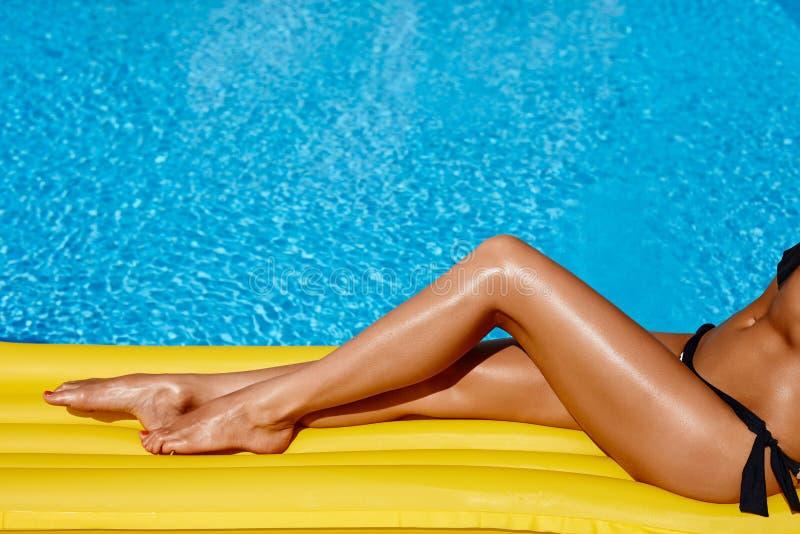 Portret van het mooie gelooide vrouw ontspannen in bikini in zwembad De benen sluiten omhoog De rode pedicure van het gelpoetsmid stock fotografie