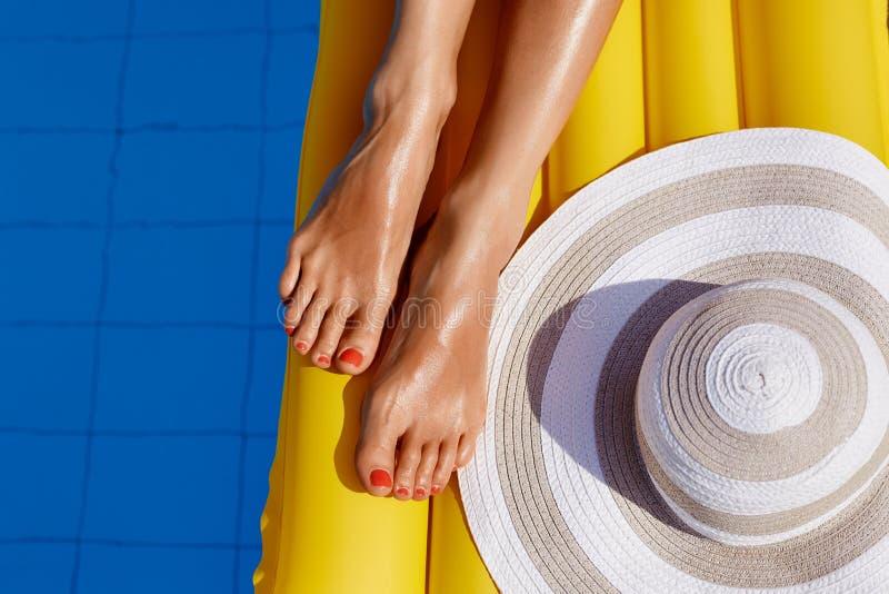 Portret van het mooie gelooide vrouw ontspannen in bikini in zwembad De benen sluiten omhoog De rode pedicure van het gelpoetsmid royalty-vrije stock afbeeldingen