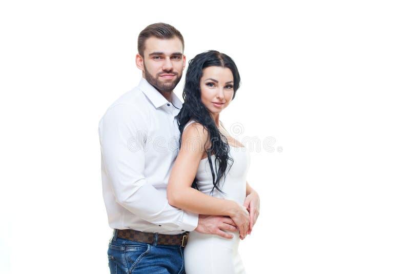 Portret van het mooie het glimlachen paar stellen bij studio over witte achtergrond Het thema van de valentijnskaartendag stock fotografie