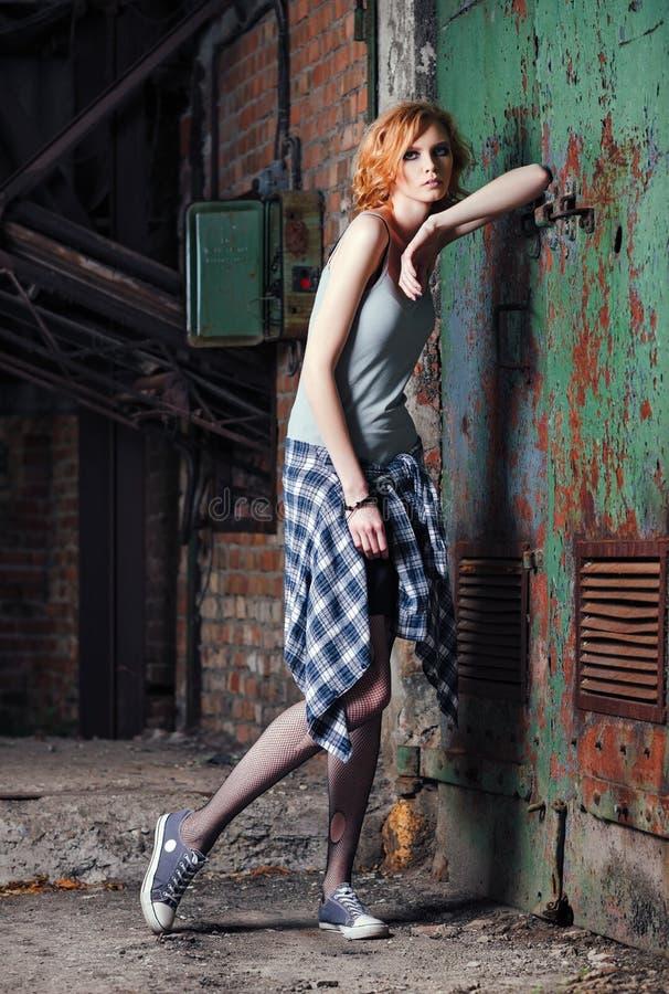 Portret van het mooie jonge meisje van de grungerots in geruit overhemd en gescheurde nylonkousen royalty-vrije stock fotografie
