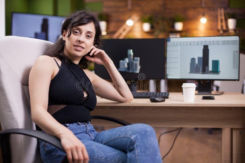 Portret van het mooie jonge vrouw glimlachen aan de camera in haar bureau stock afbeelding
