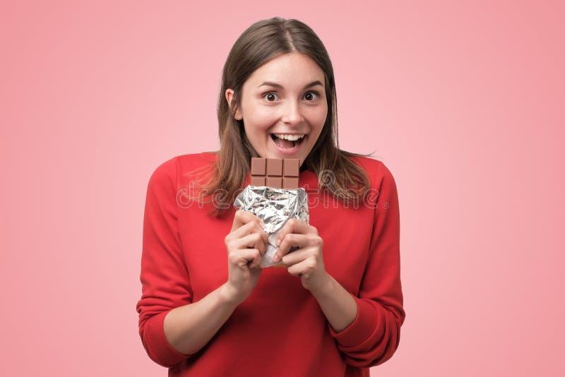 Portret van het mooie Kaukasische meisje die chocolade eten stock afbeelding