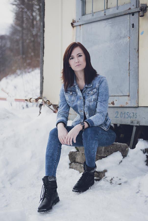 Portret van het mooie mannequin stellen aan camera en het zitten van op de steen vooraan de caravan in de wintertijd Volledig lic stock fotografie