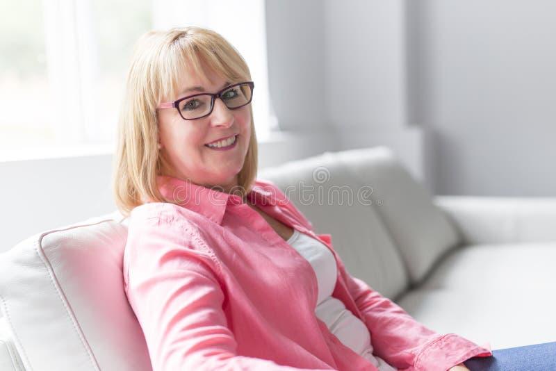 Portret van het mooie middenleeftijds rijpe hogere vrouw stellen op een bank thuis stock fotografie