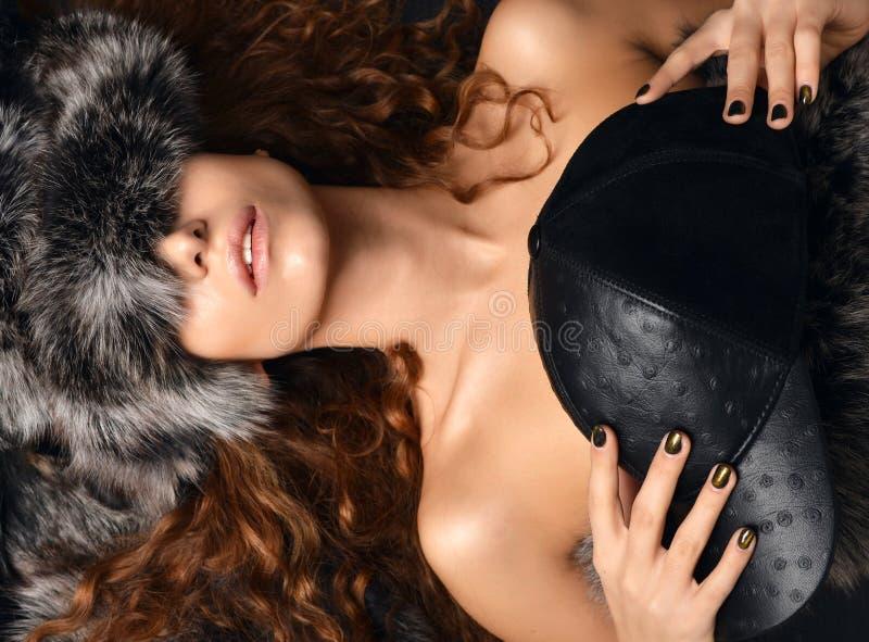 Portret van het mooie sexy donkerbruine krullende vrouw liggen met bont a royalty-vrije stock afbeeldingen