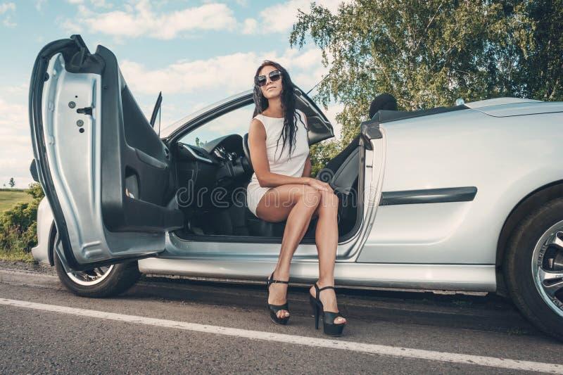 Portret van het mooie sexy model van de maniervrouw in witte kleding en luxetoebehoren die in luxeauto zitten Blauwe hemel en aut royalty-vrije stock foto's