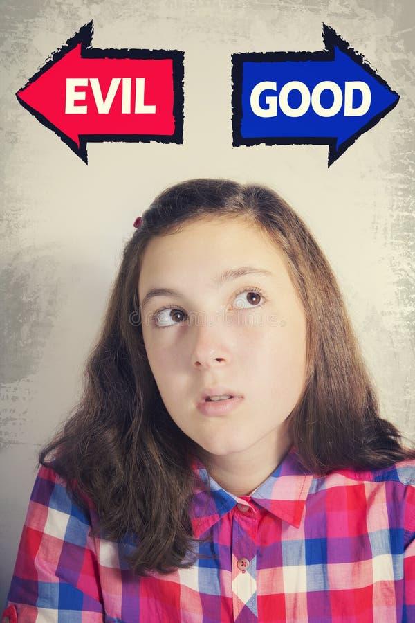 Portret van het mooie tiener kiezen tussen GOED en EVI stock foto's
