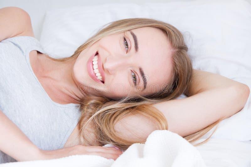 Portret van het mooie vrouw wekken in haar wit bed en geeuw Rust, slaap, mensen en comfortconcept stock afbeeldingen