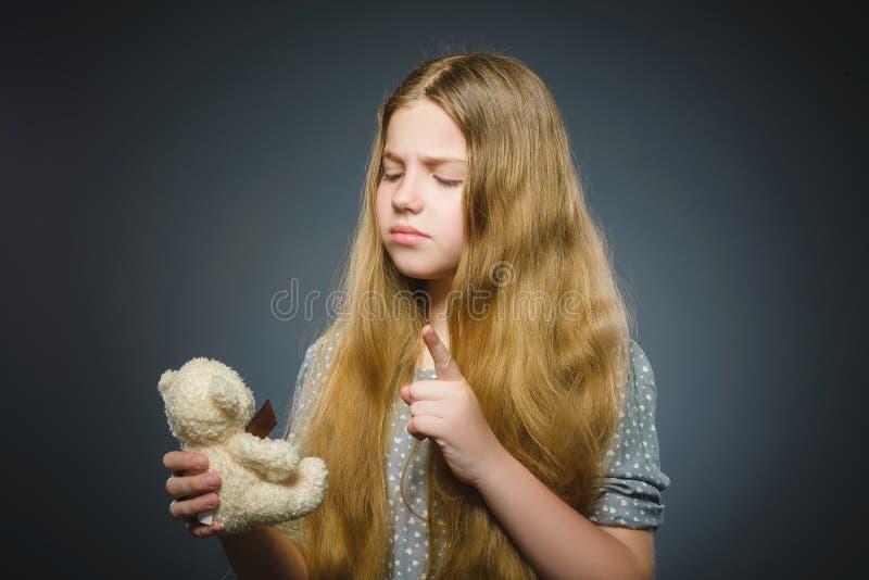 Portret van het ongerust gemaakte die meisje spelen met teddybeer op grijs wordt geïsoleerd stock foto