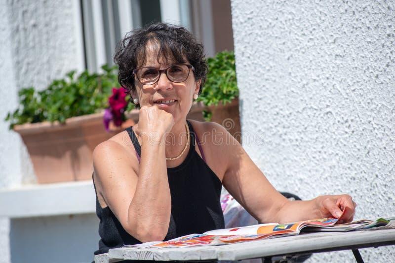 Portret van het rijpe tijdschrift van de vrouwenlezing in de tuin stock fotografie