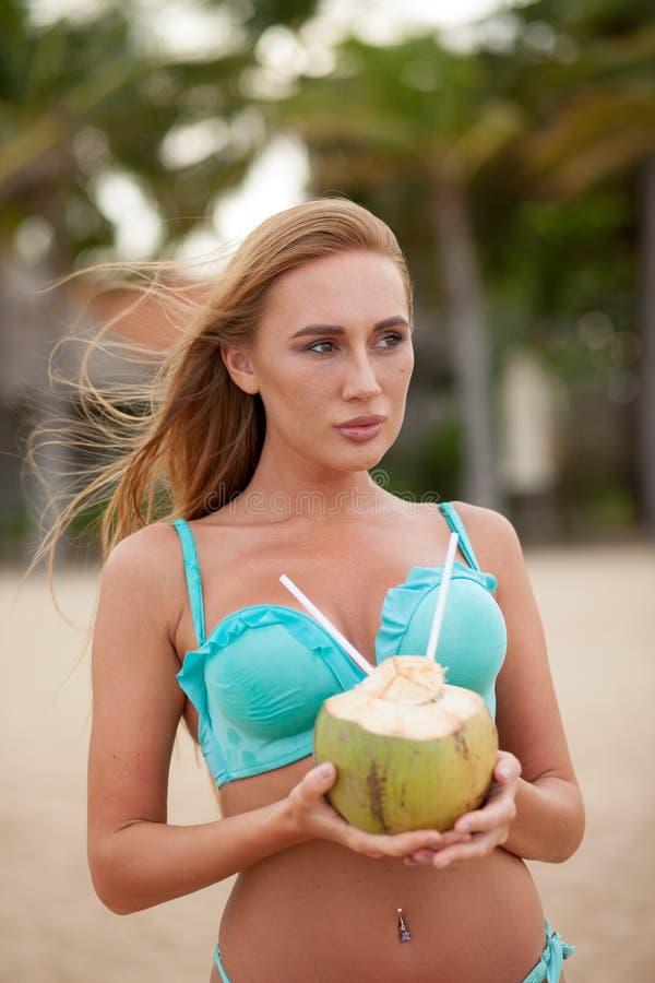 Portret van het sexy bikini jonge vrouw stellen met groene kokosnoot op het strand dichtbij palmen vietnam royalty-vrije stock foto's