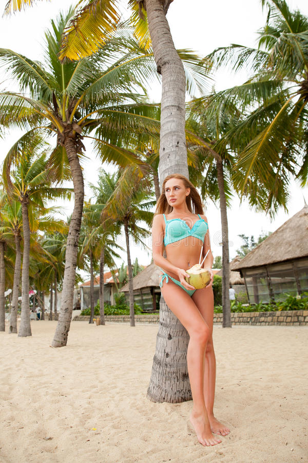Portret van het sexy bikinivrouw stellen met groene kokosnoot op het strand dichtbij palmen vietnam stock foto's