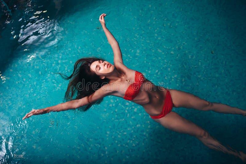Portret van het slanke jonge vrouw ontspannen in zwembad die op rug drijven royalty-vrije stock foto