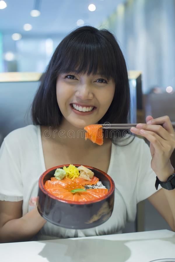 Portret van het smilling van jonge Aziatische vrouw die Japans voedsel eten stock foto